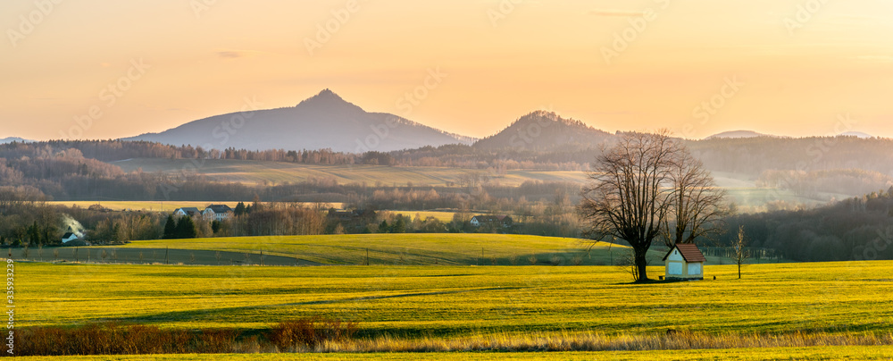 Fototapeta Hilly landscape with small chapel under the tree illuminated by evening sunset. Green grass fields and hills on the horizont. Vivid spring rural countryside. Ralsko Mountain, Czech Republic