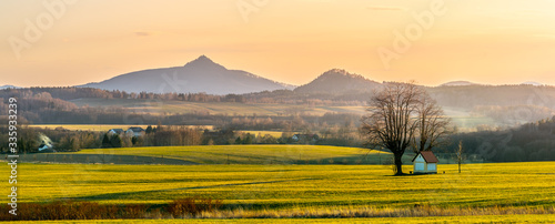 Hilly landscape with small chapel under the tree illuminated by evening sunset. Green grass fields and hills on the horizont. Vivid spring rural countryside. Ralsko Mountain, Czech Republic