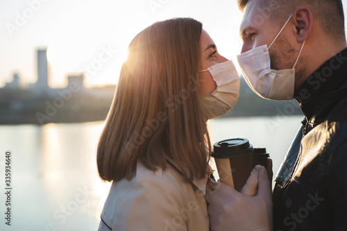 Photographie Young couple, a man and a woman in medical masks and gloves, drink coffee from disposable cups on the street and look at each other against the background of the river and the city