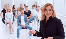 Smiling Business Woman Standing In Conference Room