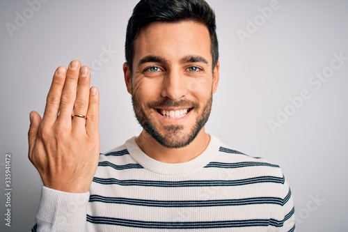 Handsome man with beard showing alliance ring marriage on finger over white back Canvas Print