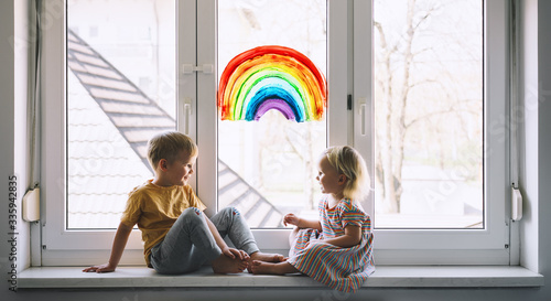 Fotografía Little children on background of painting rainbow on window