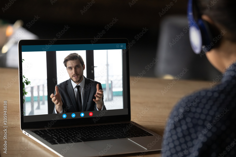 Fototapeta Woman wear headphones listen tutor during online class pc screen view over trainee shoulder. Colleague express opinion share ideas working together on project using video call, e-learn e-coach concept