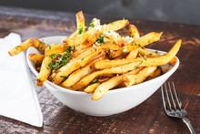 A View Of A Bowl Of Rustic Garlic French Fries, In A Restaurant Or Kitchen Setting.