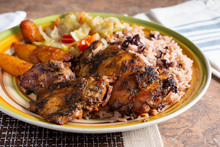 A View Of A Plate Of Jerk Chicken, In A Restaurant Or Kitchen Setting.