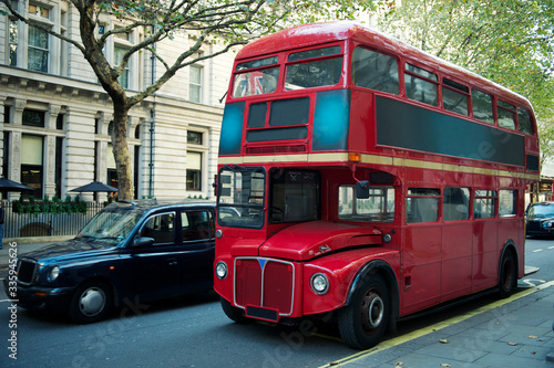 Traditional red double-decker Routemaster bus, introduced in 1956, making its wa фототапет