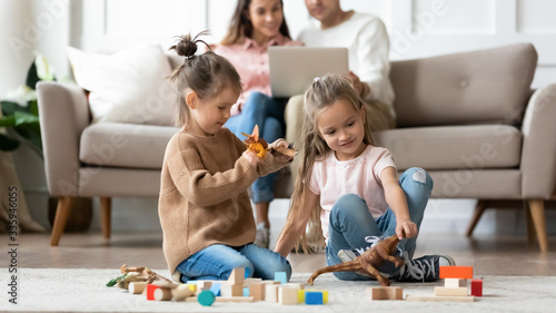 Focus on happy little sisters playing on floor carpet with toys dinosaurs, while parents resting on sofa using computer tablet Canvas