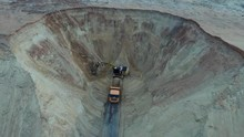 Excavator And Dumper Truck. Aerial View Of Loading Sand Into A Truck. A Heavy Machinery - Excavator And Truck Are Working In The Sand Quarry.