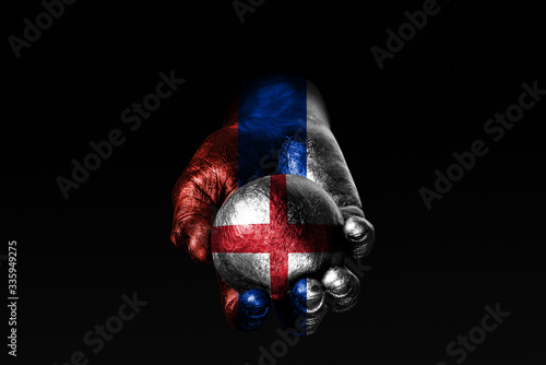 A hand with a drawn Russia flag holds a ball with a drawn England flag, a sign of influence, pressure or conservation and protection Canvas Print