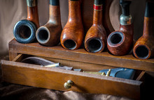 A Wooden Pipe Rack Holds Pipes...