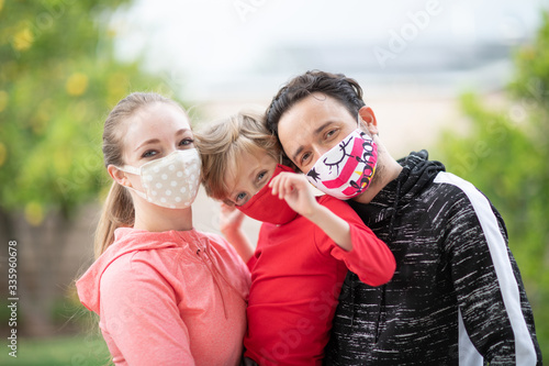 Carta da parati Family members embracing each other, smiling in the camera wearing cloth face masks