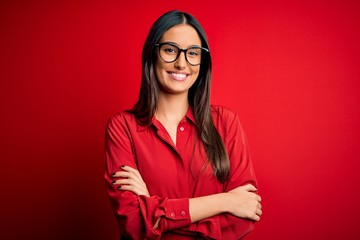 Young beautiful brunette woman wearing casual shirt and glasses over red background happy face smiling with crossed arms looking at the camera. Positive person.