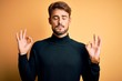 Young handsome man with beard wearing turtleneck sweater standing over yellow background relax and smiling with eyes closed doing meditation gesture with fingers. Yoga concept.