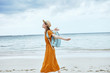 canvas print picture - young woman in white dress walking on the beach