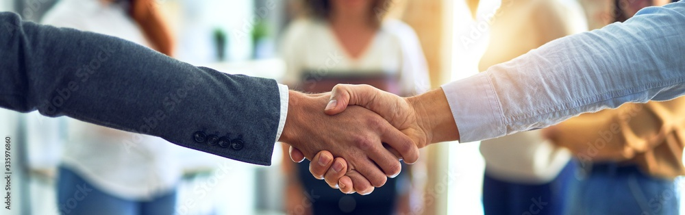 Fototapeta Group of business workers standing together shaking hands at the office