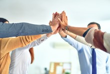 Group Of Business Workers Standing With Hands Together Highing Five At The Office