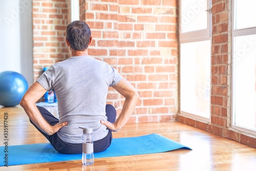 Photo Middle age handsome sportman sitting on mat doing stretching yoga exercise at gy
