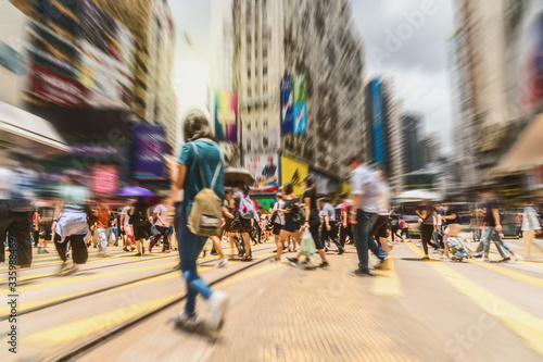 Fototapeta Blurred Crowd of Traffic car and tram with Unrecognizable pedestrians walking around crossing Central District in rush hour working day, Hong Kong, blur business and people of Pedestrian concept obraz