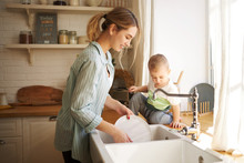 Indoor Shot Of Cute Positive Young European Female With Ponytail Posing In Kitchen Interior Washing Dishes, Her Adorable Baby Son Sitting At Sink, Turning On Tap, Helping Mother To Do Housework