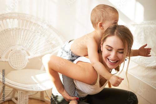 Photo Smiling adorable teenage girl babysitting little boy, giving him piggyback ride at home