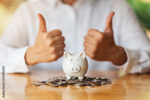 Fototapeta A woman making and showing thumbs up hand sign with coins and piggy bank on the table for saving money concept obraz