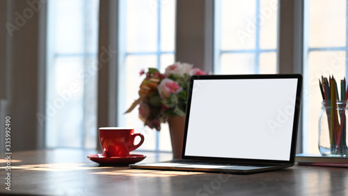 Fotografering Mockup laptop computer putting on working desk with bunch of flowers, notebook and pencil holder over comfortable wooden table