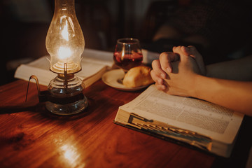 Christian people pray before taking communion together at home in the night with a vintage lamp and holy bible on wooden table, devotional or Easter concept