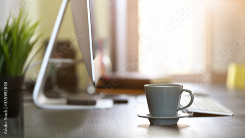 Obraz sunlight shining through windows as coffee morning on workspace. - fototapety do salonu