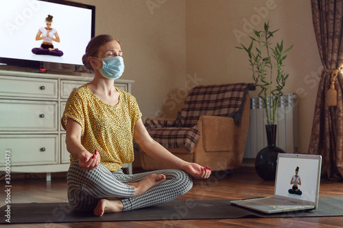 Fotografía Sporty young woman taking yoga lessons online and practice at home while being quarantine