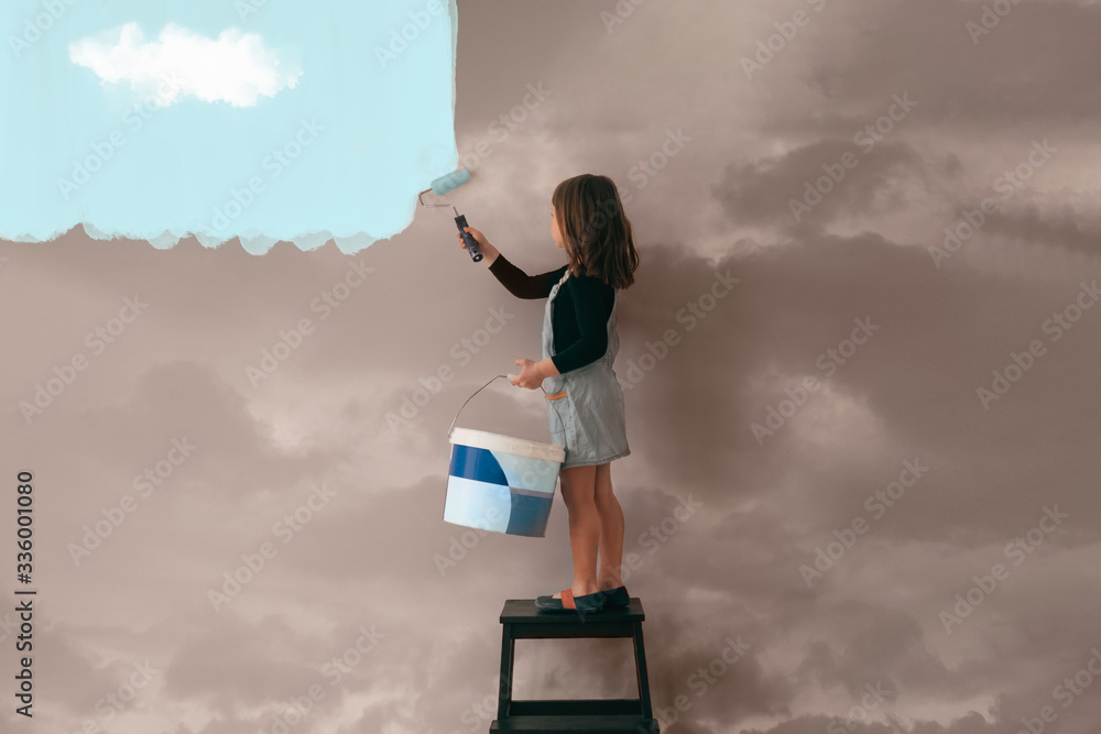 Fototapeta little girl uses a can of paint to color the wall of the room from cloudy gray to clear blue sky - positive attitude, vibes and mentality concept