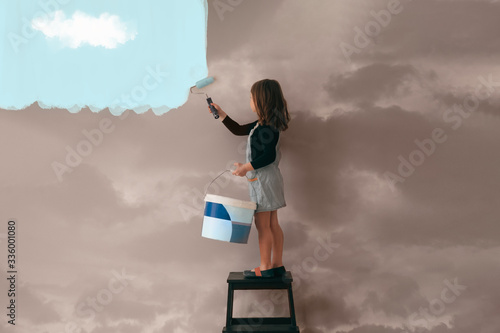 Obraz little girl uses a can of paint to color the wall of the room from cloudy gray to clear blue sky - positive attitude, vibes and mentality concept - fototapety do salonu