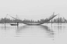 Black & White Image Of A Traditional Fisherman Under His Nets On The Thu Bon River, Hoi An, Vietnam At Dawn.