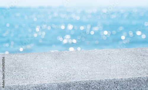 Fototapeta summer background.Empty diagonal grey pebble stone table with blur sea and sky boekh background,banner mockup template for display of product obraz
