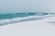 Winter sea at noon. On the beach lies snow, a cold turquoise sea. Slight fog over the sea and gray sky