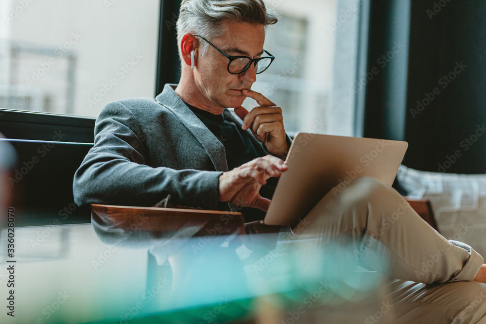 Fototapeta Businessman reading emails in office lobby