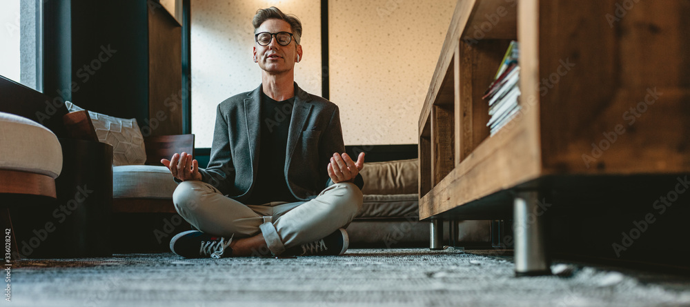 Fototapeta Mature businessman doing yoga meditation in office lounge