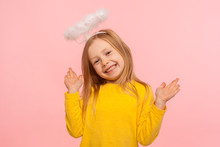 Playful Angelic Little Girl Raising Arms And Looking At Camera With Toothy Smile, Gesturing Oops, I Don't Know, It Wasn't Me, Joyful Child Denying Guilt. Indoor Studio Shot Isolated On Pink Background