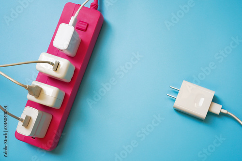 Fotografie, Obraz White mobile charger plugs full occupied on pink extension power strip and one p