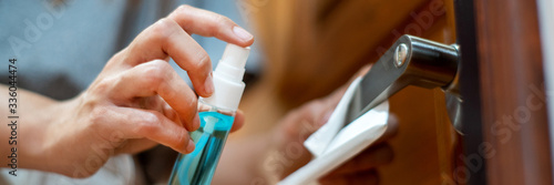 Fototapeta woman hand disinfecting the door handle by spraying a blue sanitizer from a bottle for Covid-19 Coronavirus prevention. obraz