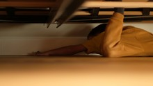 Side View Of Little Boy Lying On Floor Under Bed And Reaching Lost Toy While Spending Time In Cozy Bedroom At Home