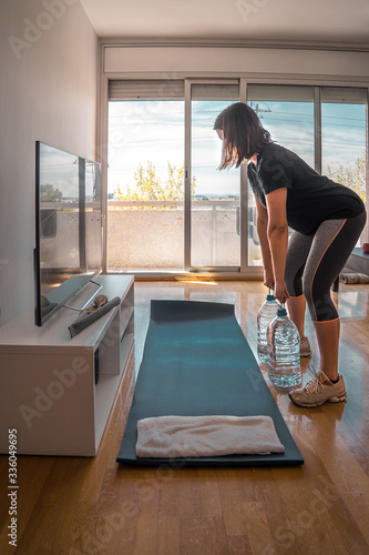 girl exercising lifting five liters water bottles in her home living room Fototapete