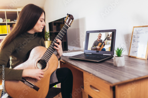 Fototapeta Focused girl playing acoustic guitar and watching online course on laptop while practicing at home. Online training, online classes. obraz