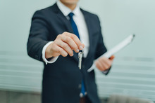 Real Estate Agent Holding Keys And Contract Agreement. In Office. Concept For Real Estate, Sale, Moving Home, Renting Property. Selective Focus