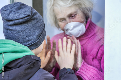Valokuvatapetti Grandmother in a respiratory mask plays with hands with her grandson through a window