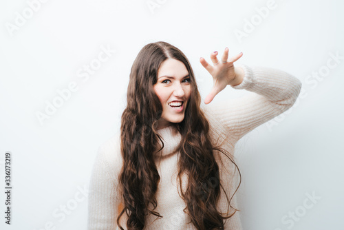 Photographie cheerful brunette girl growls like a tiger on a white background