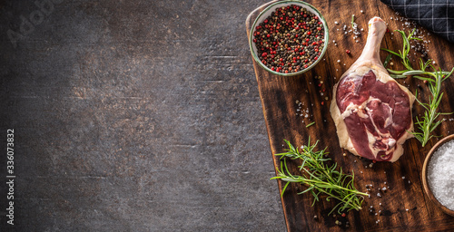 Fotografering Top view of duck leg preparaton in a dark rustic environment with wooden cutting