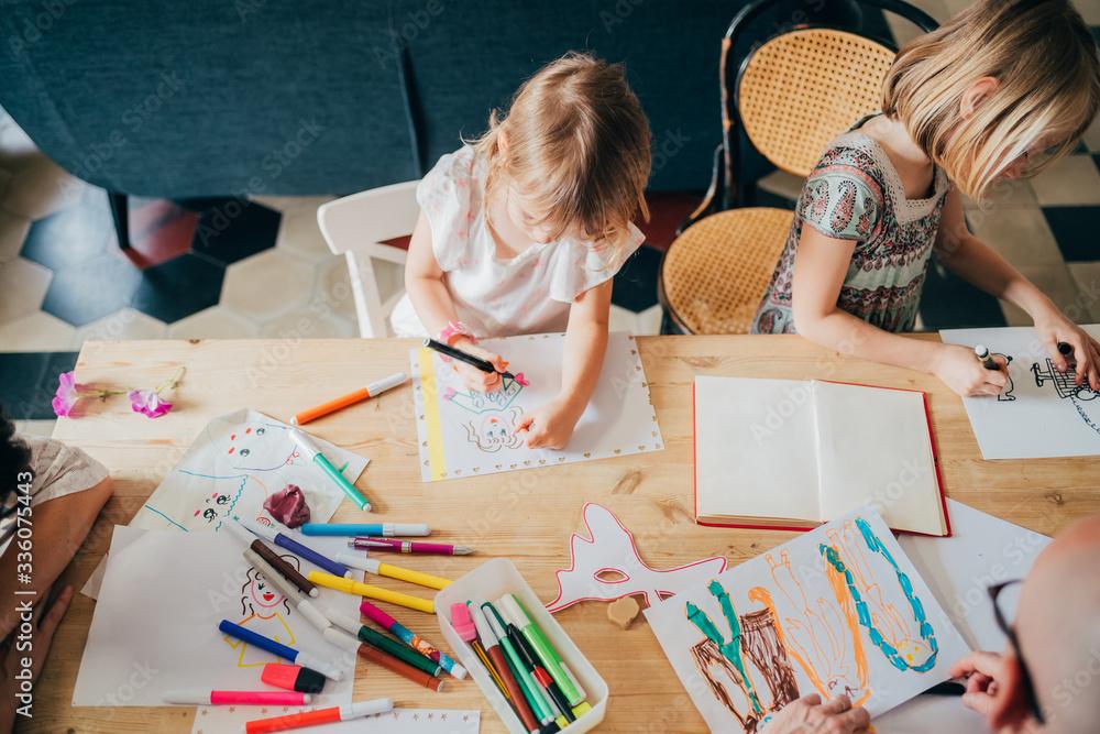 Fototapeta Top view two preschooler female children indoor at home drawing