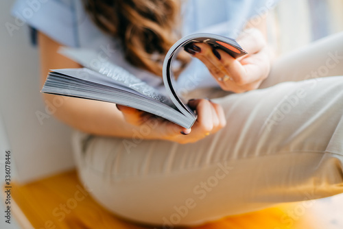 home and leasure concept - smiling woman reading magazine at home near the windo Fototapeta