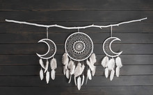 White Dream Catcher With Feather Hanging At Black Wooden Background