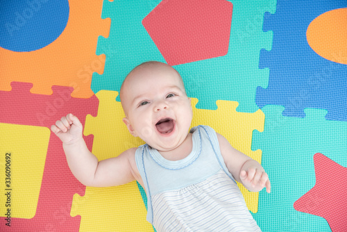 Obraz Laughing child on a colored rubber mat puzzle for playing foam with geometric figures - fototapety do salonu